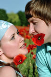 Lovers on the field with poppies Stock Image