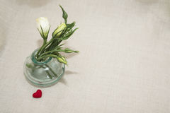 Lovers. Flowers in a glass vase for your favorite and red heart for her Royalty Free Stock Photography