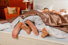 Lovers foot poking out bed covers sleeping Royalty Free Stock Photography