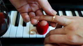 Lovers get married, exchange engagement ring on the background of a piano, a glass of red wine and a red box in the form of a stock photography