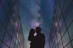 Lovers between glass buildings at night Royalty Free Stock Image