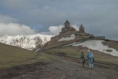 Lovers go to the Holy Trinity Church in Gergeti, Georgia Royalty Free Stock Images
