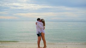 Lovers guy and girl run towards each other along the beach stock footage