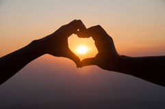 Lovers hands in heart shape with sunset background Stock Photography