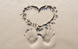 Lovers hands printed in sand Royalty Free Stock Images