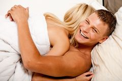 Lovers happy in bed hugging each other Royalty Free Stock Photography