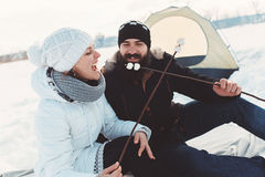 Lovers have a good time at winter holiday. In love couple in warm clothes sitting in the snow, in the background a tourist tent, Lovers laugh and enjoy the rest Royalty Free Stock Image