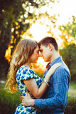 Lovers having touched their heads are in the last rays of the sun on the field. A loving couple looking at each other in the last rays of the sun, in a field in Stock Images