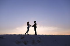 Lovers hold each other arms and swirl on sandy hill in desert on Stock Image