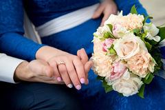 Lovers hold hands and wedding bouquet. Lovers love holding hands with a bouquet of beige flowers Royalty Free Stock Photography