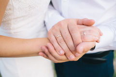 Lovers holding hands with gold wedding rings Royalty Free Stock Photography