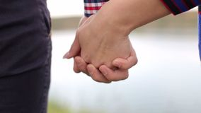 Lovers holding hands in nature close-up. Close-up of the hands of a couple in love. Lovers holding hands in nature close-up stock footage