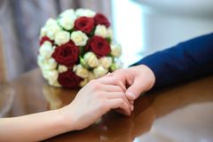 Lovers holding hands on the table. The lovers gently holding hands on the table with the wedding bouquet Royalty Free Stock Images