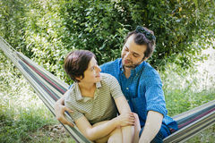 Lovers hug hammock. Lovers on hammock embracing and cuddles outdoor in the garden Stock Photography