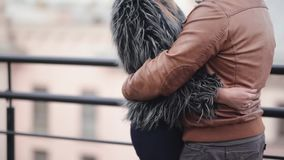Lovers hug on a roof, smile, enjoy time together. Brunette girl with long hair in a fur coat and a brunette handsome man. In a jacket in cold weather stock video footage