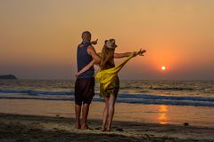 Lovers hugging against sunset on the sea. Young couple standing on a beach and admiring to sunset royalty free stock photo