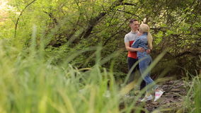 Lovers hugging while standing on rocks in river. Loving couple hugs and kisses standing on the rocks in a shallow river in the wild. Young couple standing in stock video