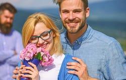 Lovers hugs outdoor flirt romance relations. Couple in love dating while jealous bearded man watching wife cheating him. Lovers hugs outdoor flirt romance stock photo
