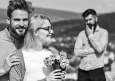 Lovers hugs outdoor flirt romance relations. Couple romantic date lovers bouquet flowers. Couple in love dating while. Jealous bearded men watching wife stock photos