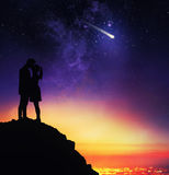 Lovers kiss under the starry sky. Couple of lovers in backlight from above a mountain expresses a desire during the sight of a falling star stock photos