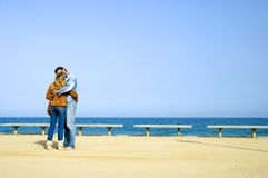 Lovers kissing. Trendy couple kissing with the sea in the background Stock Images