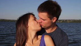 Lovers kissing on the beach. Young couple kissing on the beach on a sunny day stock video footage