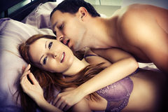Lovers kissing in bed Royalty Free Stock Images