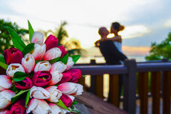 Lovers. Kissing on the bridge, in front of tulips stock photo