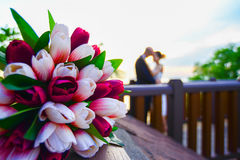 Lovers. Kissing on the bridge, in front of tulips royalty free stock photo