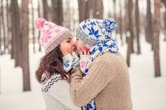 Lovers kissing on a date in winter Park Stock Image