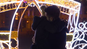 Lovers kissing and hugging in downtown Christmas market in nighttime stock video footage