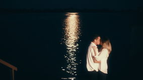 Lovers kissing in the sea in the moonlight.  stock footage