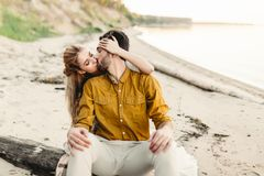 A lovers is kissing. Young couple is having fun and hugging on the beach. Beautiful girl embrace her boyfriend from back Stock Image