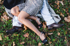 Lovers legs embrace. Engaged couple's legs embrace on a patch of grass Stock Photography