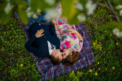 Lovers lie on a blanket in a spring garden Stock Photo