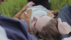Lovers lie on the meadow and talk. Merry smile. Lovers lie on the meadow and rest. View from above. A pair of lovers walking around the park in an embrace. Two stock video footage
