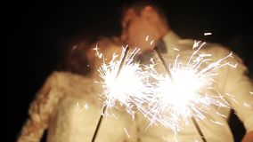 Lovers lighting sparklers, celebrating wedding and kiss in blur
