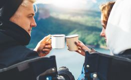 Lovers looking at each other, couple enjoy together of sun flare mountain, travelers drink tea on cup enjoy nature, romantic look. On background of panoramic royalty free stock photography