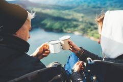 Lovers looking at each other, couple enjoy together of sun flare mountain, travelers drink tea on cup enjoy nature, romantic look royalty free stock photo