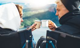 Lovers looking at each other, couple enjoy together of sun flare mountain, travelers drink tea on cup enjoy nature, romantic look. On background of panoramic royalty free stock images