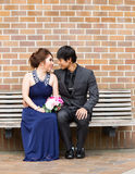 Lovers looking at each other while sitting on bench Stock Photo