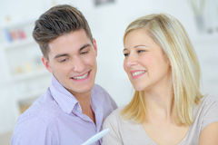 Lovers looking at pregnancy test at home Stock Image