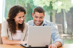 Lovers looking at their laptop at home Stock Images