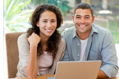 Lovers looking at their laptop at home Royalty Free Stock Photography