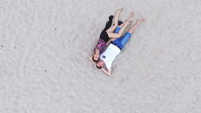 Lovers lying on the sand near the sea - girl stretches the hand upwards.  stock video