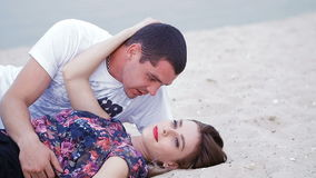 Lovers lying on the sand near the sea - love story.  stock footage