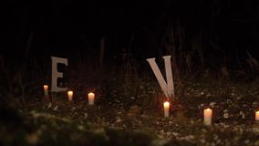 Lovers man and girl go on road night of Park lit candles, the inscription in white letters love stock footage