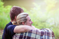 Lovers man and woman embrace in a plaid in the sunset. A married couple beautiful girl and boyfriend hugging in plaid plaid in the forest in the sunset light Royalty Free Stock Image