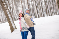 Lovers man and woman having fun and playing in winter Park. Royalty Free Stock Photo