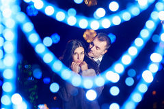 Lovers man and woman in park with evening lights Royalty Free Stock Image